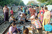 Selling fish from the train tracks at Thamaing station on 17th May 2016 in Yangon, Myanmar.  Thamaing is one of the 39 stations on the Yangon Circular Railway, Myanmar. The railway, a narrow gauge local commuter trail network serving Yangon metropolitan area is a 28.5 mile 45.9 km 39 station loop system. This British built rail-loop connects Yangon to its satellite towns and villages