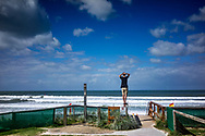 Male figure standing on a post looking out to sea on the Gold Coast in Australia.