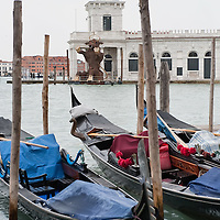 VENICE, ITALY - FEBRUARY 04:   Gondolas rest on the Grand Canal facing Punta della Dogana where a model of a giant bull - the 2012 edition symbol of Venice Carnival - has been placed on February 4, 2012 in Venice, Italy. The Carnival of Venice (Carnevale di Venezia) is an annual festival and starts 40 days before Easter and ends on Shrove Tuesday ( Martedì Grasso).  (Photo by Marco Secchi/Getty Images)