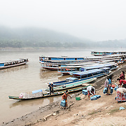 A group of women disembark from a sampan having crossed the Mekong River near Luang Prabang to head to the morning market nearby.