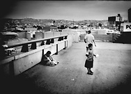 Younger brother begs for change, on pedestrian bridge over the Tijuana River that leads from Mexico / US border point of entry to Zona Norte, while his brother plays ranchero music on the accordion, Tijuana, Mexico.