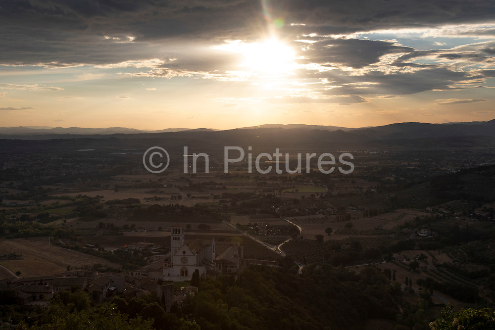 View at sunset over the Basilica of San Francesco dAssisi and the valley to the west in Assisi, Umbria, Italy. The Papal Basilica of Saint Francis of Assisi is the mother church of the Roman Catholic Order of Friars Minor Conventual in Assisi, a town of Umbria region in central Italy, where Saint Francis was born and died. The basilica is one of the most important places of Christian pilgrimage in Italy. Assisi is a town in the Province of Perugia in the Umbria region, on the western flank of Monte Subasio. It is generally regarded as the birthplace of the Latin poet Propertius, and is the birthplace of St. Francis, who founded the Franciscan religious order in the town in 1208, and St. Clare, Chiara dOffreducci, the founder of the Poor Sisters, which later became the Order of Poor Clares after her death. Assisi is now a major tourist destination for those sightseeing or for more religious reasons.
