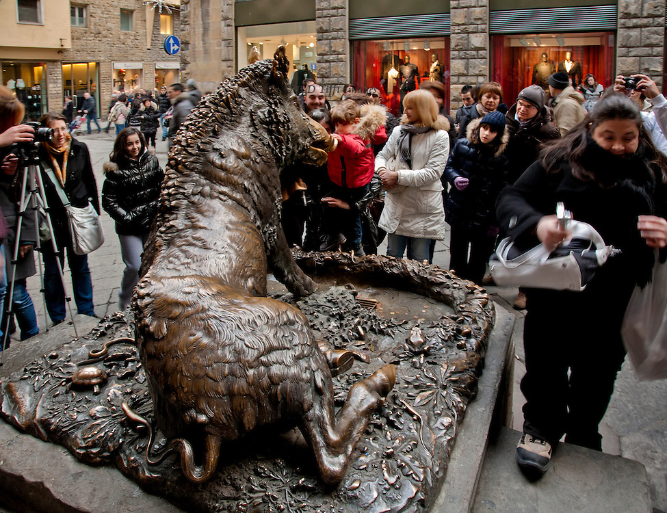 """Bronze statue of the boar (""""Il Porcellino"""") in the Mercato Nuovo, seen from behind it as a smiling group of people gather round and a boy in a red jacket rubs its nose for luck.  One man has camera on a tripod, another woman walks by with her point-and-shoot camera.  Illuminated boutique show windows beyond."""