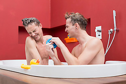 Homosexual couple having fun in bathtub, smiling