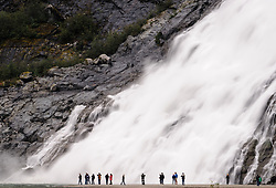 Hikers to Nugget Falls located next to the Mendenhall Glacier near Juneau, Alaska are dwarfed by the 377 foot waterfall. Each year, 465,000 curise ship passengers visit the Mendenhall Glacier.