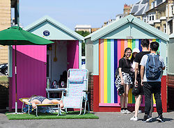 © Licensed to London News Pictures. 03/07/2018. Hove, UK. Tourists take photographs of themselves as a woman  sleeps in front of a colourful beach huts on the seafront at Hove, East Sussex on the south coast of England, as a heatwave continues across the UK. Photo credit: Ben Cawthra/LNP