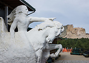 This plaster Crazy Horse Memorial 1/34th scale model (16 feet high by Korczak Ziolkowski in 1964) is being carved into Thunderhead Mountain (seen beyond) on private land in the Black Hills, between Custer and Hill City, 17 miles from Mount Rushmore, in Custer County, South Dakota, USA. In progress since 1948, the monolithic sculpture is far from completion. It depicts the Oglala Lakota warrior, Crazy Horse, riding a horse and pointing into the distance. The memorial was commissioned by Henry Standing Bear, a Lakota elder, to be sculpted by Korczak Ziolkowski. It is operated by the nonprofit Crazy Horse Memorial Foundation. The sculpture is planned to be of record-setting size: 641 feet wide and 563 feet high. The head of Crazy Horse will be 87 feet high (whereas the heads of the four U.S. Presidents at Mount Rushmore are each 60 feet high). Crazy Horse (1840–1877) was a Native American war leader of the Oglala Lakota. He took up arms against the United States federal government to fight against encroachment by white American settlers on Indian territory. He earned great respect from both his enemies and his own people in several battles of the American Indian Wars on the northern Great Plains, including: the Fetterman massacre in 1866, in which he acted as a decoy, and the Battle of the Little Bighorn in 1876, in which he led a war party to victory. Four months after surrendering in 1877, Crazy Horse was fatally wounded by a bayonet-wielding military guard, while allegedly resisting imprisonment at Camp Robinson in present-day Nebraska. In 1982 he was honored by the U.S. Postal Service with a 13¢ Great Americans series postage stamp.