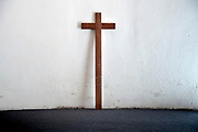 simple wooden cross leaning against a white wall in a church Naples Italy