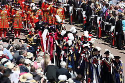 The Yeomen Warders of Her Majesty's Royal Palace march behind members of the Royal Family and The Knights of the Garter during the annual Order of the Garter Service at St George's Chapel, Windsor Castle.