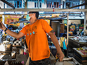 04 JANUARY 2016 - BANGKOK, THAILAND:  A worker takes down a lighting fixture in Bang Chak Market after the market closed permanently. The market closed January 4, 2016. The Bang Chak Market serves the community around Sois 91-97 on Sukhumvit Road in the Bangkok suburbs. About half of the market has been torn down. Bangkok city authorities put up notices in late November that the market would be closed by January 1, 2016 and redevelopment would start shortly after that. Market vendors said condominiums are being built on the land.       PHOTO BY JACK KURTZ