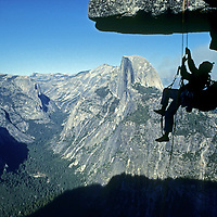 John Fischer ascends a rope below Glacier Point, Yosemite National Park, California.  Half Dome rises above Tenaya Canyon in the background.