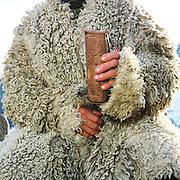 Shepherd Simion Dobrin wears a sheepskin cloak and holds 'coaja', a locally made sheep's milk cheese wrapped in birch bark, Valea Urdii, Romania