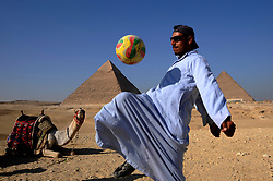 A man who hires camels to tourists, passes the time playing football beside the pyramids on November 6, 2009, in Giza, Egypt.