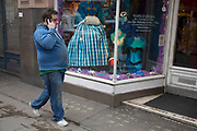 Large man in blue walks past a shop window of a costume shop, and seems to blend in with the colours. London, UK.