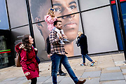 A young girl and some adults walk beneath the large billboard, a portrait of English football player, Marcus Rashford, outside the Strand branch of Coutts Bank, on 14th October, 2021, in Westminster, London, England. Marcus Rashford has recently been awarded an honourary degree by The University of Manchester in recognition of his political campaigning on behalf of the underprivilged in particular, of school meals and his philanthropy. He currently plays for Manchester United and is in the English national team. He has also been the victim of online racial abuse.