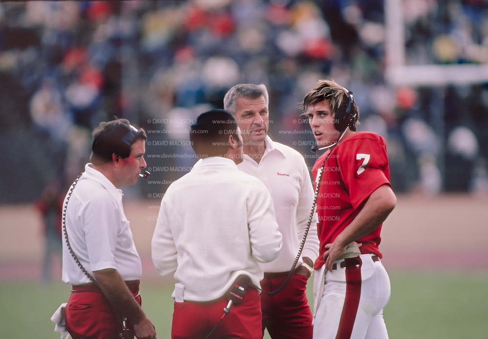 PALO ALTO, CA - OCTOBER 1981:  Quarterback John Elway of Stanford University plays in an NCAA football game against UCLA  on October 10, 1981 at Stanford Stadium in Palo Alto, California.  Visible at left is Coach Dick James, at right without headset is Head Coach Paul Wiggin.  Photo by David Madison | www.davidmadison.com