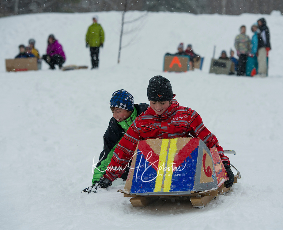 """Seth and Sander Valpey try to get some momentum going on their """"Thing 3"""" sled during Gilford Parks and Recreation's annual Cardboard Derby at the Outing Club on Wednesday morning.  (Karen Bobotas/for the Laconia Daily Sun)"""
