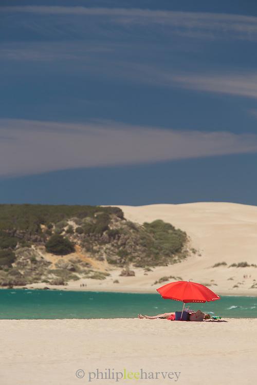 Woman under umbrella on Bolonia beach in Cadiz, Spain
