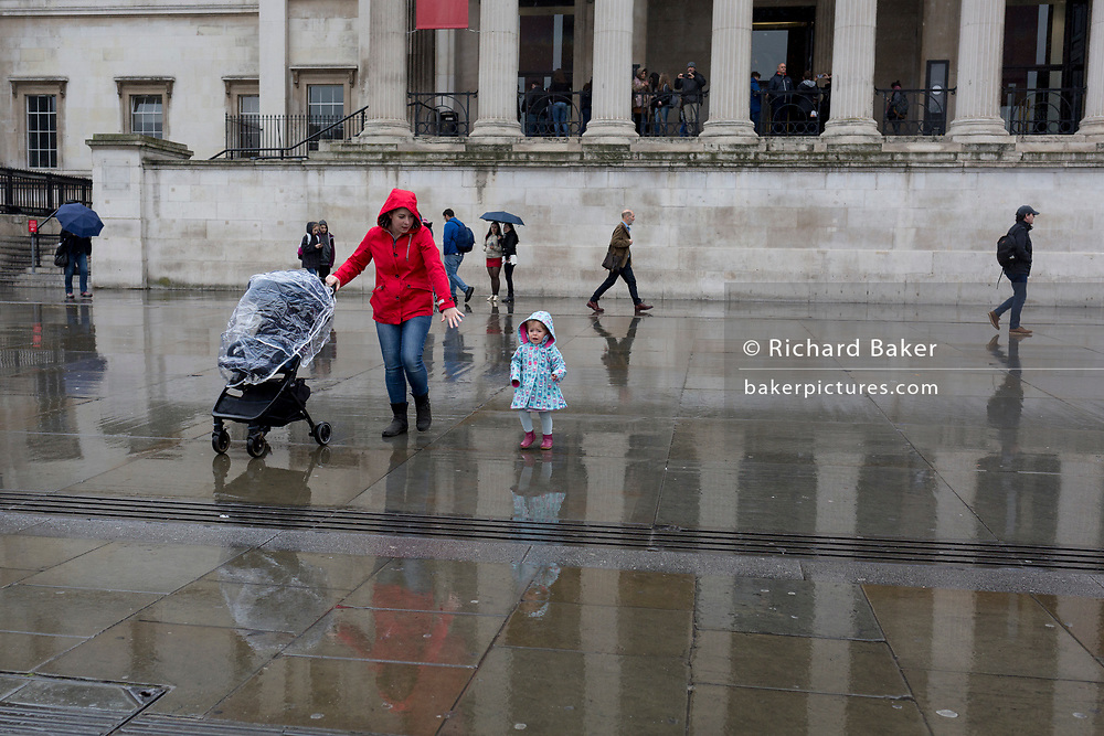 A mother guides her unhappy young child beneath the columned architecture of the National Gallery in Trafalgar Square, Westminster, on 9th April 2019, in London, England.