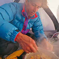 Jan-Marc Baker cooking in tent in Sierra Nevada, John Muir Wilderness, California.