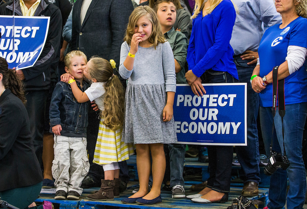 A young girl kisses a young boy as they await Canada's Prime Minister and Conservative leader Stephen Harper to attend a campaign event at the Martin Family Fruit Farm in Waterloo, October 12, 2015.  Canadians will go to the polls for a federal election on October 19.