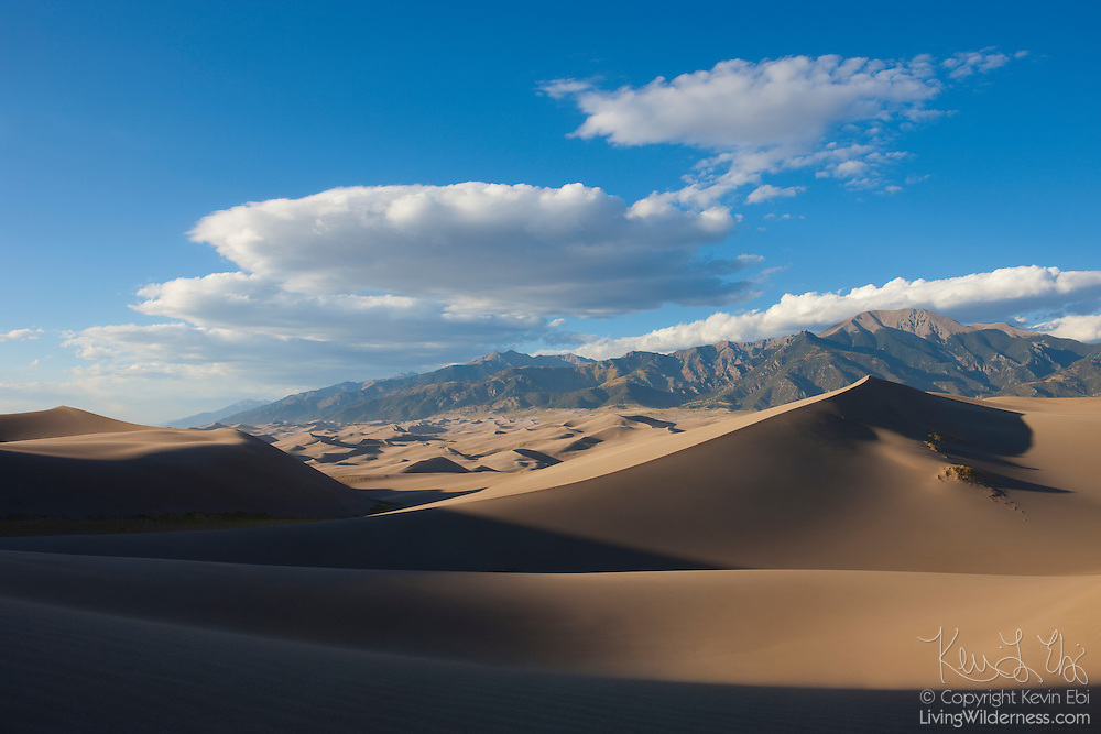 Hundreds of tall sand dunes form at the base of the Sangre de Cristo Mountains in Great Sand Dunes National Park, Colorado. Strong winds blow the sand from as much as 65 miles (105 km) away. These mountains block the wind's path, causing the sand to pile up in dunes.