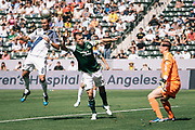 Los Angeles Galaxy midfielder Marcelo Sarvas, left, heads the ball towards the goal over Portland Timbers midfielder Jack Jewsbury, middle, and Timbers goalkeeper Troy Perkins during the first half of an MLS soccer match, Sunday, June 17, 2012, in Carson, Calif. (AP Photo/Bret Hartman)