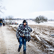 After crossing the Macedonian-Serbian border a young refugee walks the unofficial refugee route. Near Miratovac, Serbia, January 2016.<br /> <br /> According to UNHCR, 67,415 refugees landed in Greece in January 2016 alone, the majority of who traveled the route through Serbia on their way to Western Europe. The number of refugees arriving in Greece has dropped significantly since the Balkan border closed to refugees in March 2016.