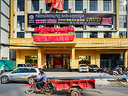"""13 FEBRUARY 2019 - SIHANOUKVILLE, CAMBODIA: A worker hauling construction materials goes past the BWin Casino, a newly opened casino in downtown Sihanoukville. There are about 80 Chinese casinos and resort hotels open in Sihanoukville and dozens more under construction. The casinos are changing the city, once a sleepy port on Southeast Asia's """"backpacker trail"""" into a booming city. The change is coming with a cost though. Many Cambodian residents of Sihanoukville  have lost their homes to make way for the casinos and the jobs are going to Chinese workers, brought in to build casinos and work in the casinos.      PHOTO BY JACK KURTZ"""