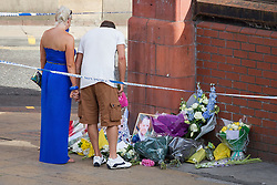 © Licensed to London News Pictures . 14/07/2013 . Manchester , UK . An unidentified man and woman allowed through the police cordon to lay flowers and tributes at the scene where a fire fighter, identified as Stephen Hunt, died while tackling a fire in a store-room of Paul's Hair World in Oldham Street, Manchester. Two 15-year-old girls arrested on suspicion of manslaughter. Photo credit : Joel Goodman/LNP