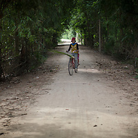 A young woman farmer in Cambodia cycles along a path