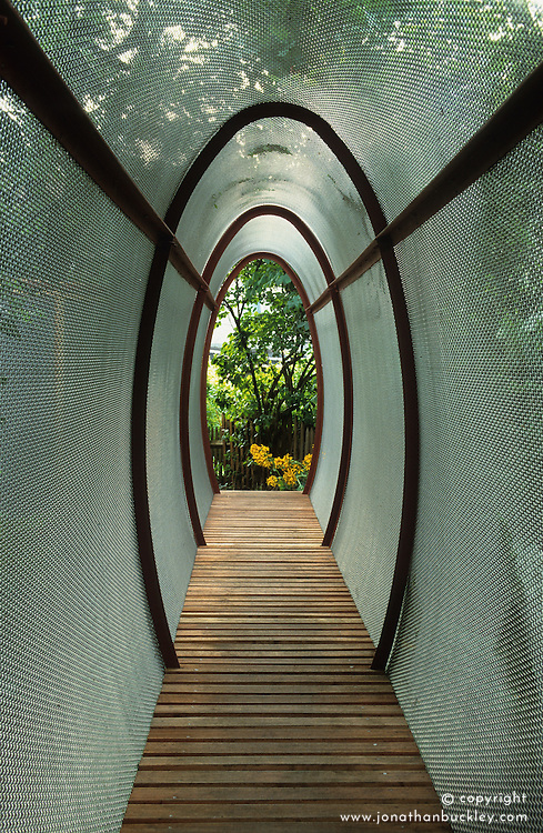 Oval, wire mesh tunnel with slatted wooden flooring.