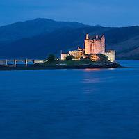 Lights illuminate Eilean Donan castle as night falls over Loch Duich, Scotland