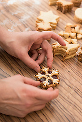 Hand placing snowflake cookie top of whipped marmalade cookie, Munich, Bavaria, Germany