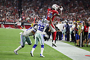 Arizona Cardinals wide receiver Jaron Brown (13) leaps while trying to catch a fourth quarter pass while being pushed out of bounds by Dallas Cowboys cornerback Orlando Scandrick (32) and Dallas Cowboys outside linebacker Damien Wilson (57) during the 2017 NFL week 3 regular season football game against the Dallas Cowboys, Monday, Sept. 25, 2017 in Glendale, Ariz. The Cowboys won the game 28-17. (©Paul Anthony Spinelli)