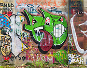 Street art painting in old mill building in Vernonia, Oregon depicting green creatures, one with red tongue