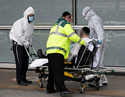 **Face has been pixelated to hide the identity of patient** <br /> © Licensed to London News Pictures. 02/04/2020. London, UK. Ambulance workers wearing personal protective clothing and a medical face masks transports a patient in to The Royal London Hospital in East London, during a pandemic outbreak of the Coronavirus COVID-19 disease. Members of the public have been told they can only leave their homes when absolutely essential, in an attempt to fight the spread of COVID-19. Photo credit: Ben Cawthra/LNP