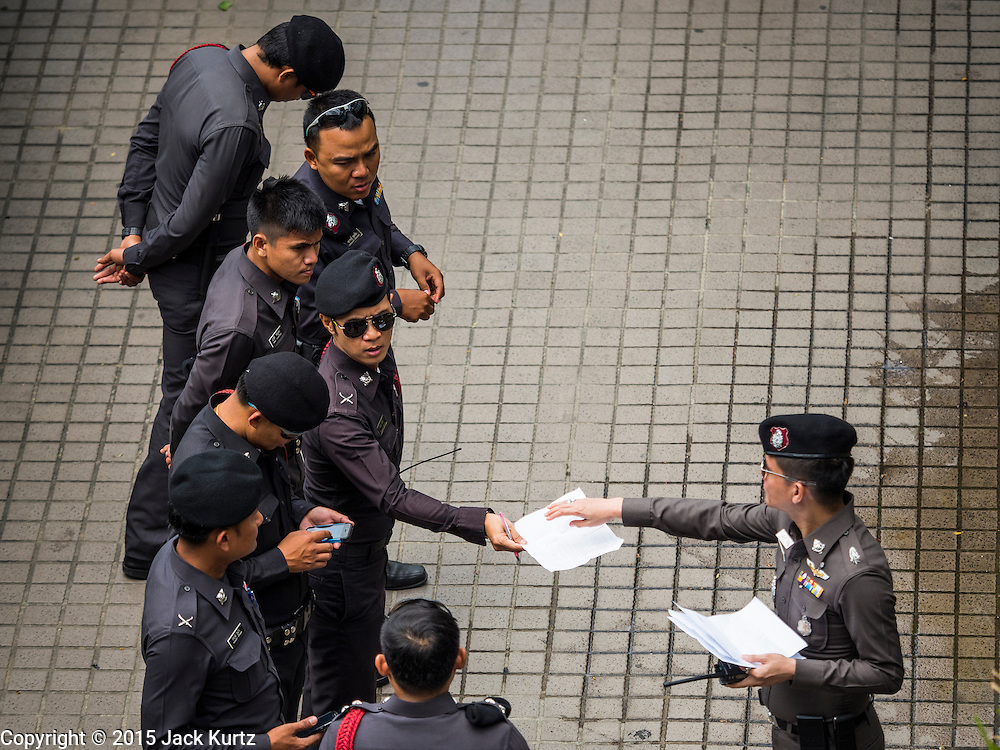 """26 JUNE 2015 - BANGKOK, THAILAND:  Thai police in front of the Foreign Correspondents' Club of Thailand after they cancelled the release of a Human Rights Watch (HRW) report, """"Persecuting 'Evil Way' Religion: Abuses against Montagnards in Vietnam"""", at the Foreign Correspondents' Club of Thailand (FCCT) in Bangkok Friday morning. The report made no mention of the human rights situation in Thailand. The Thai Ministry of Foreign Affairs (MFA) contacted HRW Thursday afternoon and asked them to cancel the program because it was a """"sensitive"""" matter that could impact on Thai-Vietnam relations. HRW told the MFA that they would go ahead with the report's release. Friday morning, before the report was scheduled to be released, Thai police officers arrived at the FCCT and cancelled the event. Phil Robertson, deputy director of Human Rights Watch's Asia division, said, """"By stepping in to defend a neighboring state's human rights violations against a group of its people and interrupting a scheduled press conference, Thailand's military junta is violating freedom of assembly and demonstrating its contempt for freedom of the press.""""      PHOTO BY JACK KURTZ"""