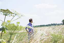 Mid adult man standing in meadow