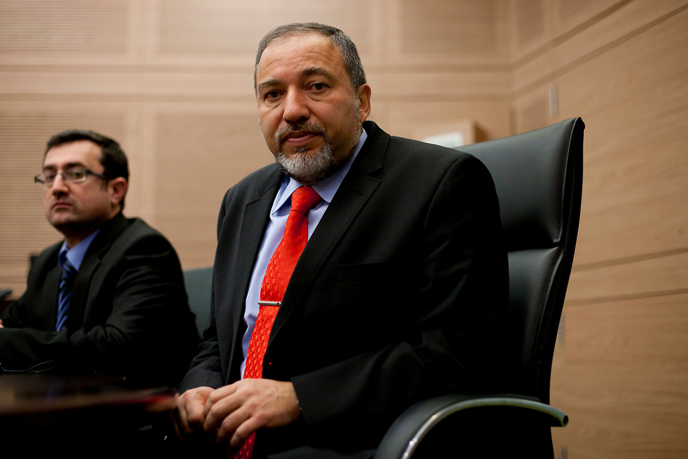 Israel's Foreign Minister Avigdor Lieberman (R) and MK Robert Ilatov attend a meeting of Yisrael Beiteinu at the Knesset, Israel's parliament in Jerusalem on December 15, 2010, after the Knesset passed a preliminary reading of a bill to certify the validity of all conversions to Judaism conducted by the IDF without the permission of the Chief Rabbinate.