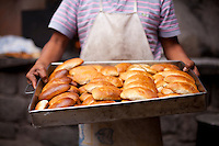 Young man holding pan of wood fired empanadas in the town of Pisac, in the Sacred Valley, Peru.