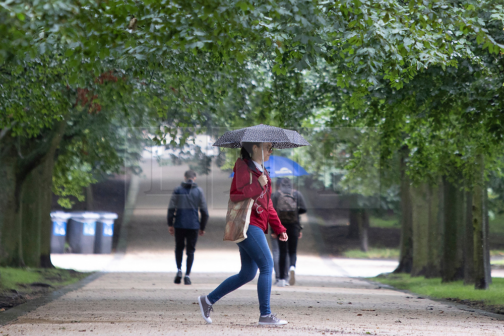 © Licensed to London News Pictures. 27/07/2021. London, UK. A woman uses an umbrella to shelter from rain in Greenwich Park in South East London. A yellow weather warning for thunderstorms is in place for parts of England. Photo credit: George Cracknell Wright/LNP