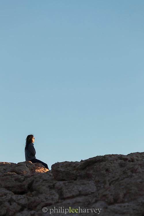 Tourist watching sunset on desert, under clear sky, Valle de la Luna, Atacama Desert, Chile