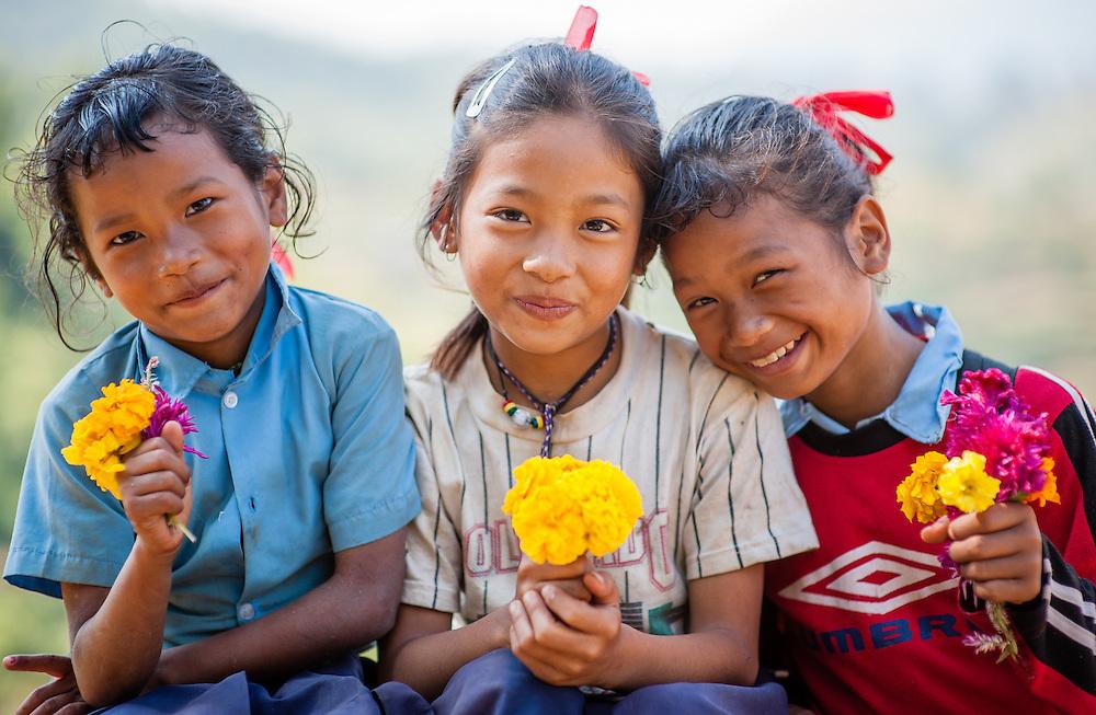 Three girls with flowers (Nepal)