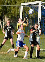 Goalie Danielle Tidd from Prospect Mountain High School goes up and makes the block ahead of Gilford's Mikala Clarke during NHIAA Division III girls soccer on Tuesday afternoon.     (Karen Bobotas/for the Laconia Daily Sun)