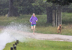 Licensed to London News Pictures. 07/08/202. London, UK. Summer washout. A runner gets caught in torrential rain in Richmond Park southwest London today as thunderstorms continue to hit the South East with further showers expected tomorrow. Yellow weather warnings for England have been issued for thunderstorms with heavy rain, and possible flooding as the bad weather is set to continue until Monday. However brighter weather is finally forecast for next week with highs of 23c. Photo credit: Alex Lentati/LNP