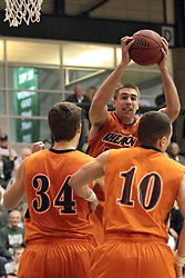 01 March 2014:  Nate Haynes pulls in a rebound while teammates Tyler Peter and Caleb DeMoss stand by during an NCAA mens division 3 CCIW  Championship basketball game between the Wheaton Thunder and the Illinois Wesleyan Titans in Shirk Center, Bloomington IL