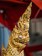 """19 DECEMBER 2016 - BANGKOK, THAILAND: A Naga (mythical serpent) on a Thai Royal Chariot at the Bangkok National Museum. A """"Spirit Appeasing"""" Ceremony was held for the Royal Chariots at the Bangkok National Museum. The chariots will be used to take the body of Bhumibol Adulyadej, the Late King of Thailand, and members of the Royal funeral cortege to the cremation site on Sanam Luang for His Majesty's cremation. This will be the first cremation of a Thai King since 1950, when King Bumibol's brother, Rama VIII, Ananda Mahidol, was cremated. The design of the royal crematorium is based on Buddhist cosmology, with the main peak of Mount Sumeru (also known as Meru in Hindu cosmology) at center and eight other peaks signifying the levels of the universe. The crematorium will be decorated with mythical creatures such as garuda, angels, and Himmapan Forest creatures. The structure and funeral pyre will stand just over 50 meters tall. The exact date of the King's cremation has not been set yet but is expected to be late next year.     PHOTO BY JACK KURTZ"""