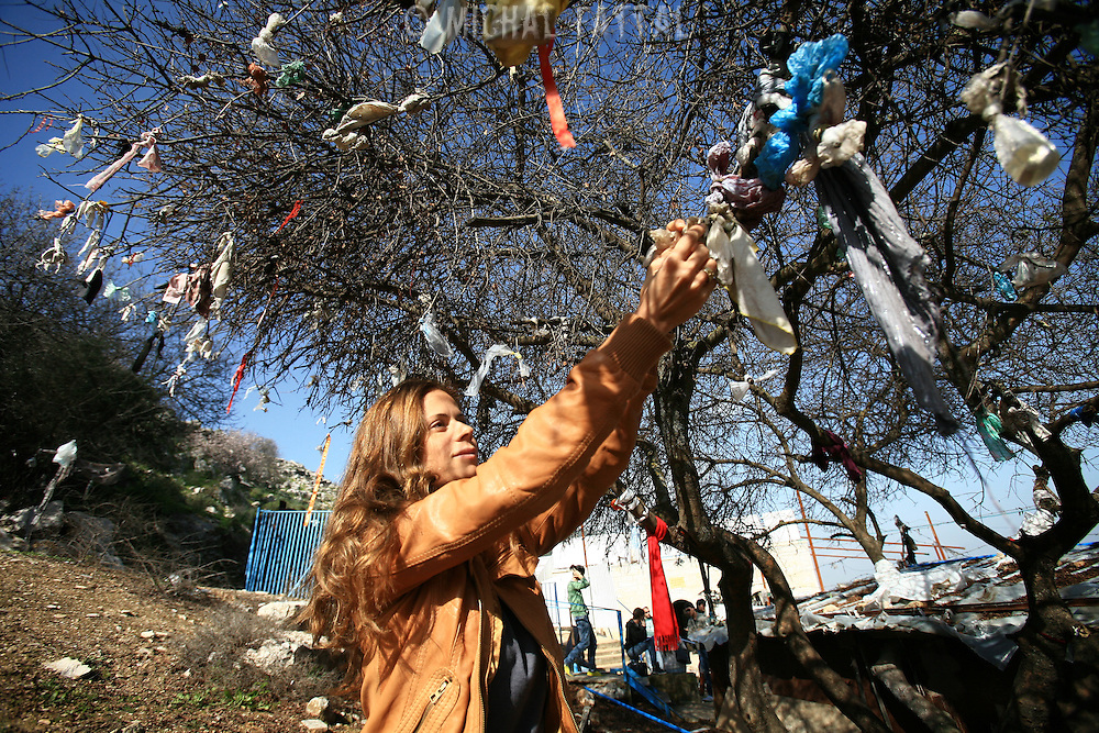 Keren, a young Jewish woman, binds a hair tie to one of the branches at the grave of Yonatan ben Uziel at Amukah in the Galilee in Israel.Over the centuries the tradition developed that those seeking for their soul-mates would be married within one year if they prayed at Rabbi Ben-Uziel's tomb.