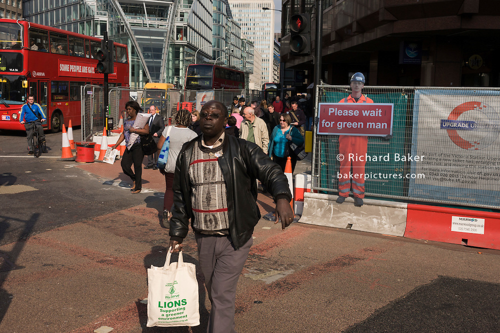 A male jaywalker crosses a road junction on a red pedestrian light in central London during temporary street improvements.